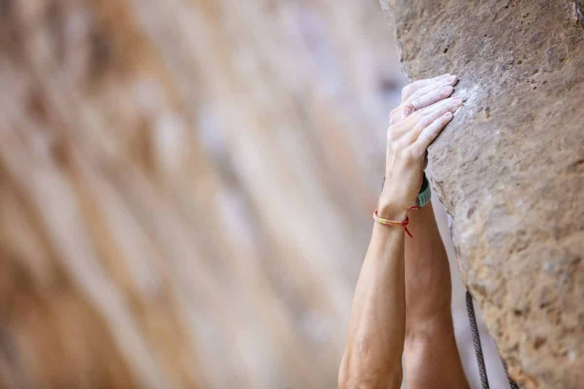 Close up climber's hands on a cliff