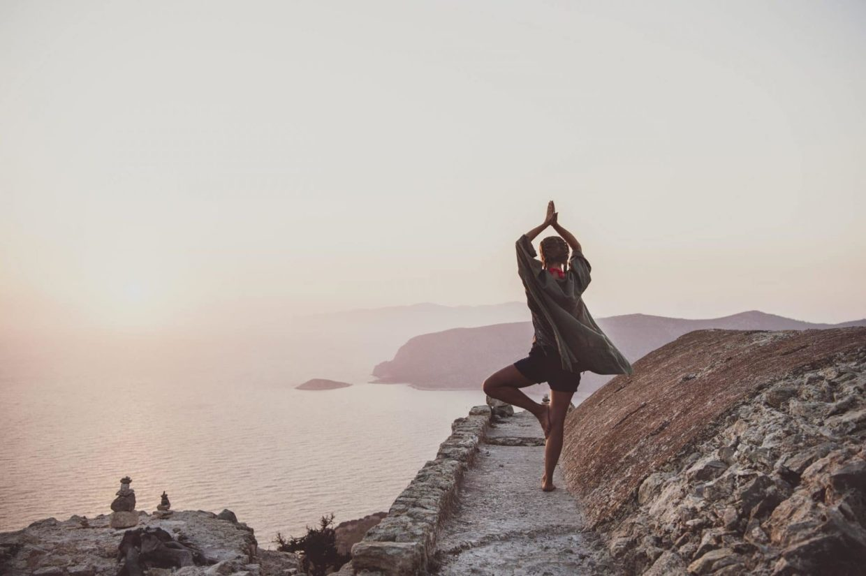 Woman standing and meditating in Monolithos, Rhodes, Greece